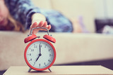 Young girl lies on the couch and stretches her hand to the red alarm clock to turn it off. Late wake up. - 226710560