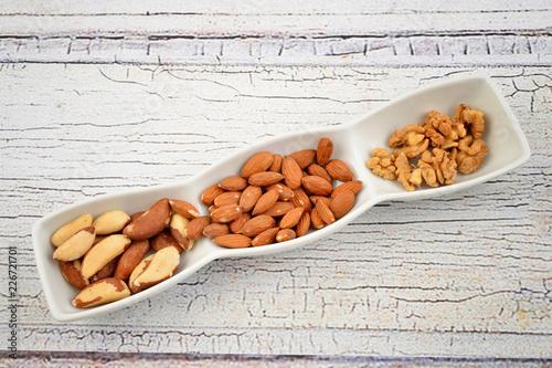 Foto Murales Nuts in bowl on rustic wooden plate.