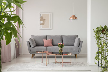 Real photo of a comfy sofa, copper coffee table and plants in a bright living room interior