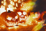 Glowing Halloween pumpkin lanterns on the table, real photo with copy space - 226722396