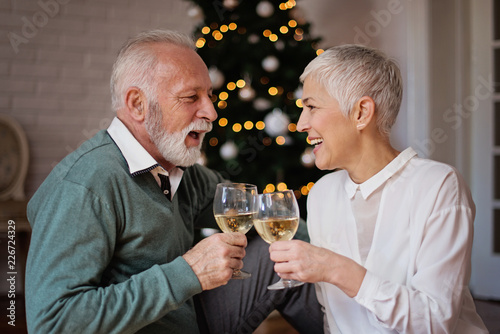 Foto Murales Senior couple cheering next to a beautiful decorated Christmas tree with ornaments