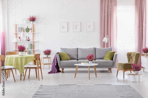 Leinwandbild Motiv Elegant daily room with round table with wooden chairs and grey sofa with olive green pillows, stylish armchair next to it, real photo