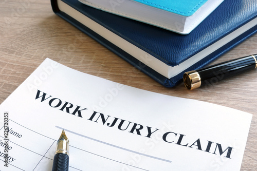 Foto Murales Work injury claim form and note pad.