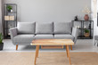 Leinwandbild Motiv Wooden table on carpet in front of grey sofa in minimal living room interior with plant. Real photo