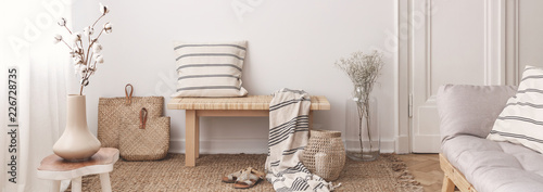 Leinwanddruck Bild Flowers on table in white living room interior with pillow and blanket on wooden stool. Real photo