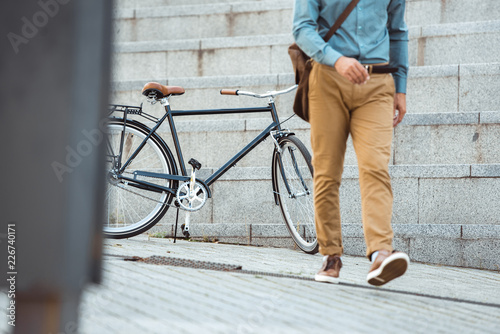 Poster low section of stylish man walking on street, parked bicycle behind