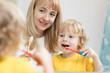 Leinwandbild Motiv mother teaching kid teeth brushing in bathroom