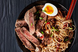 black bowl of Soba noodles with sliced roast beef - 226744125