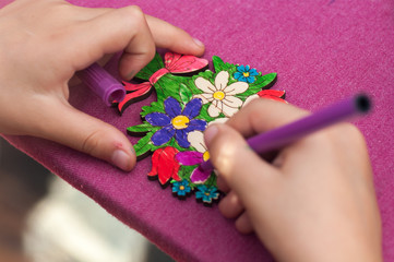child paints with a felt-tip pen drawing on a wooden board close-up
