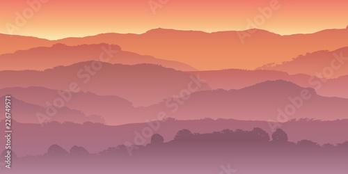 Paysage de montagne dans la brume, coloré par le soleil couchant