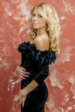 Young beautiful blonde girl in a black cocktail dress