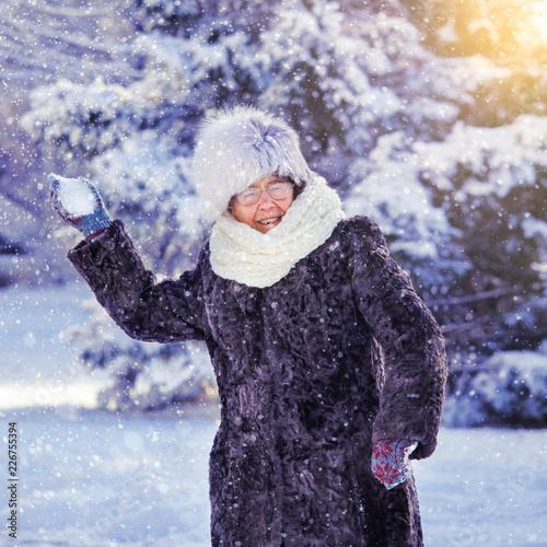 Foto Murales Old woman walking at winter park.