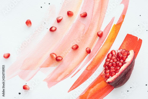 Foto Murales top view of pomegranate piece with seeds on white surface with red watercolor strokes