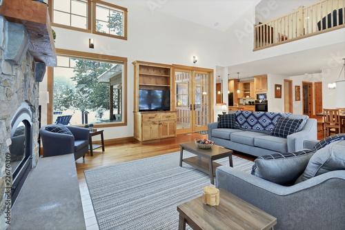 Elegancka przestrzeń mieszkalna z wysokim sklepionym sufitem i kamiennym kominkiem.