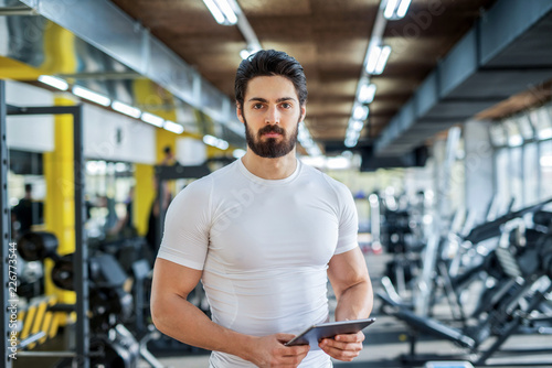 Foto Murales picture of strong handsome personal fitness trainer posing in front of the camera in bright gym.