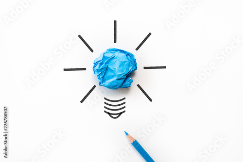 Leinwandbild Motiv Inspiration and great idea concept. light bulb with crumpled colorful paper and blue pencil on white background.
