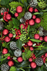 Christmas flora with holly, fir, ivy, mistletoe and pine cones with red bauble decorations forming a background. Traditional Christmas greeting card for the festive holiday season.