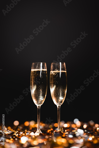 new year celebration with champagne glasses on golden confetti on black - 226803563