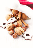 Santa Claus hat with nuts, spices and chocolates. Christmas background. White wooden background. Copy space.  - 226820515