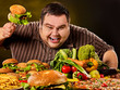 Diet fat man who makes choice between healthy and unhealthy food. Overweight male with hamburgers, french fries and vegetables on black background. Dangers of extra weight
