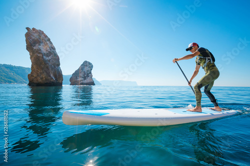 Leinwanddruck Bild Stand up paddle boarding. Young man floating on a SUP board. The adventure of the sea with blue water on a surfing.