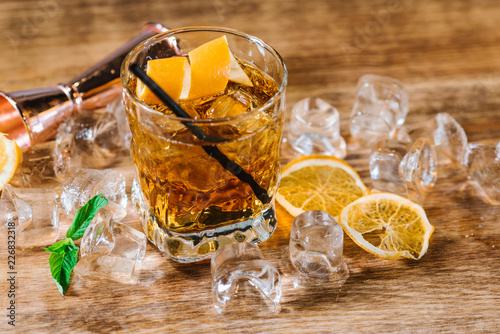 A whiskey with ice in glass on wooden table