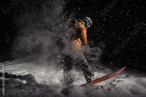 Leinwandbild Motiv Male snowboarder riding on board on a powder snow