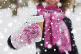 people, season, drinks and leisure concept - close up of woman hand with coffee cup outdoors in winter - 226841354