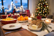 christmas dinner and eating concept - glass of red wine and food on table at home