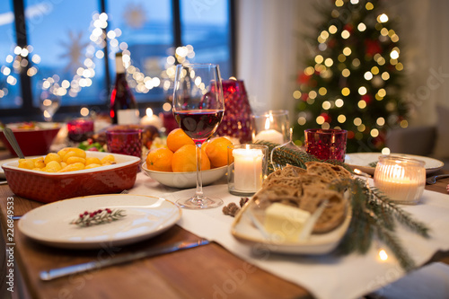 christmas dinner and eating concept - glass of red wine and food on table at home © Syda Productions
