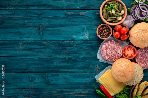 Sticker Preparation of burger. Meat, tomatoes, onions. On a blue wooden background. Top view. Free copy space.