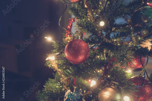 Foto Murales Retro image of shiny red Christmas bauble hanging on tree