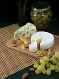 Variation of cheese, nuts and olives on a wooden platter - 226854508