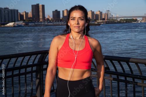 Foto Murales Healthy woman wearing sportswear listening to music outside
