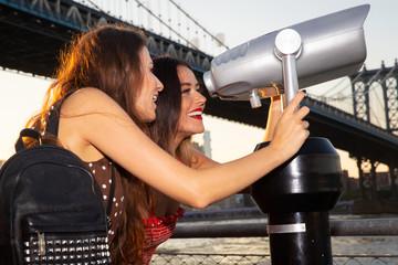 Two women in New York looking through tourist view finder under Brooklyn Bridge at Manhattan