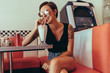 Quadro Woman sitting at a diner and sipping milkshake with a straw