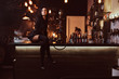 Leinwandbild Motiv Seductive brunette girl in black clothes sitting with crossed legs on counter in a nightclub.