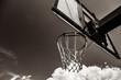 photo of the basketball hoop with clouds on background. Image in black and white color style