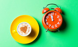 yellow cup of coffee and red clock on the green background - 226871335