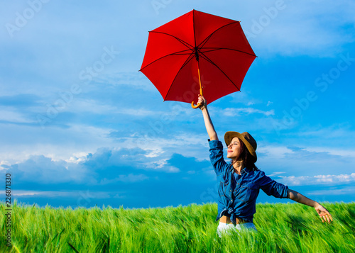 portrait of young beautiful woman with red umbrella in the field