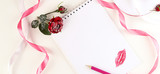Blank notepad, pencil, rose flower, pink ribbon and lips. Concept of holiday or greetings. Selective focus, top view, flat layout.