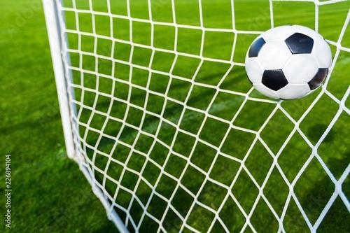 Leinwanddruck Bild A Soccer Ball in a Net