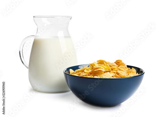 Leinwandbild Motiv Bowl with crispy cornflakes and jug of milk on white background