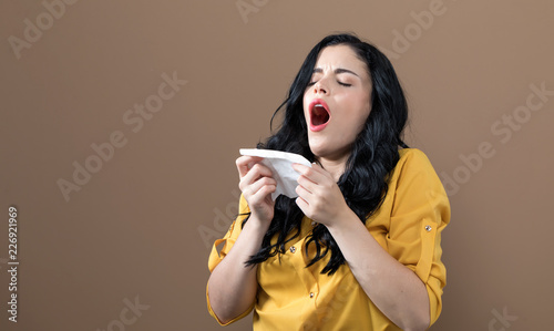Leinwanddruck Bild Sick young woman with tissues on a brown background