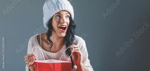 Leinwandbild Motiv Happy young woman holding a shopping bag on a gray background