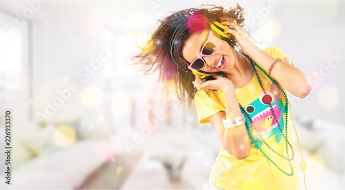 Happy young woman listening music in headphones - 226933370