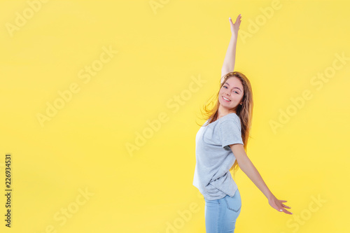 Foto Murales Girl in center of frame on yellow background raises her hands in relationship. Copy space left.