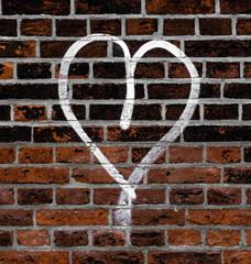 Herzgraffito auf Backsteinmauer