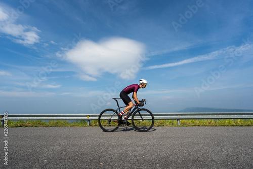 Azjatycki mężczyzna jeździć na rowerze drogowego rower w ranku