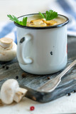 Cream-soup with champignons in an enamel mug. - 226976315